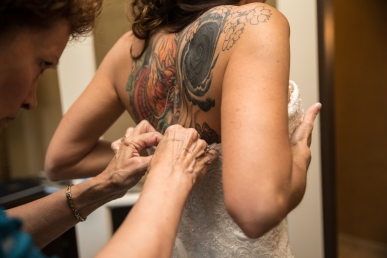 Getting ready for her big day, a bride is buttoned up into her wedding gown.